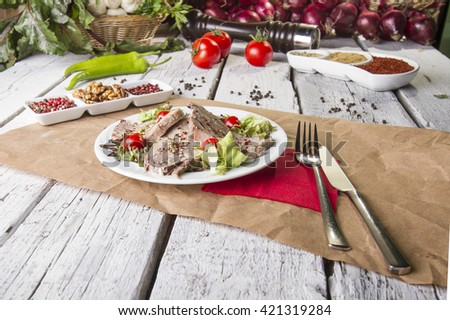Boiled beef tongue ( dil sogus ) on wood background with garnish salad top view - stock photo