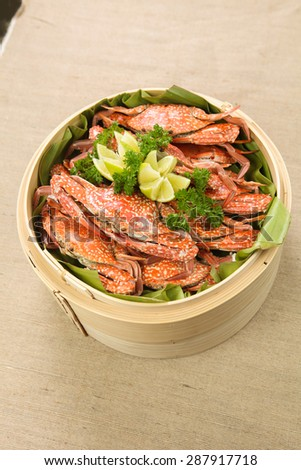 Boiled blue swimming crabs with lemon on bamboo steam pot - stock photo