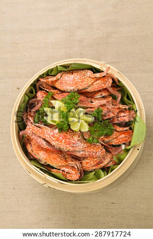 Boiled blue swimming crabs with lemon on bamboo steam pot,view from above - stock photo