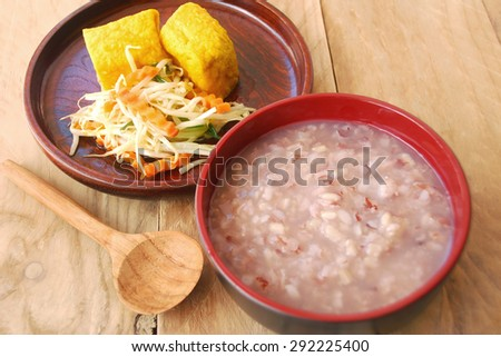 Boiled brown rice in a bowl with wood ladle and vegetarian dishes made from  bean sprouts and yellow tofu fried look appetizing. Asians prefer to eat for breakfast. - stock photo