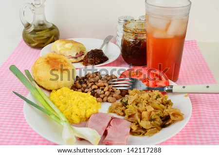 Boiled cabbage on white plate with fried ham, black-eyed peas; creamed corn and hot buttered biscuits.  Side of fig preserves, green onions, sliced tomato and glass of iced cold sweet tea. - stock photo