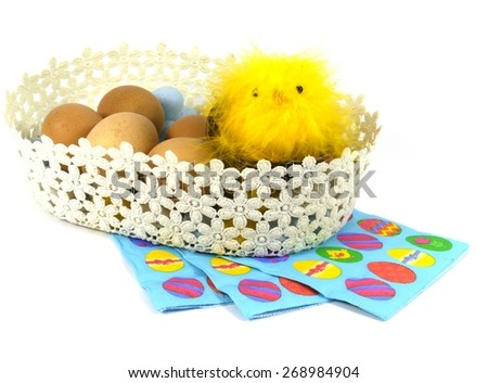 Boiled chicken eggs with a yellow Easter chick in a basket on colourful napkins over white - stock photo