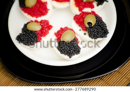 Boiled chicken eggs with black caviar, minced salmon and green olives
