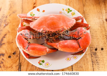 Boiled crab prepared on plate on wooden background - stock photo