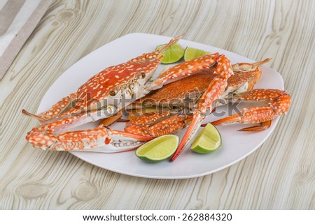 Boiled crabs with lime on the wood background - stock photo
