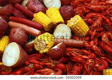 Boiled crawfish with corn, potatoes and hot dogs. - stock photo