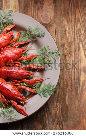 boiled crayfish on wooden surface dill. old style plate - stock photo