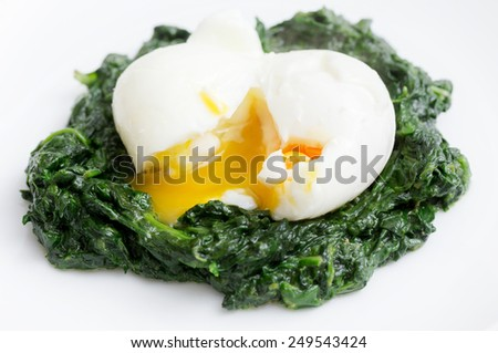 Boiled egg on a bed of spinach, an Italian recipe uova mollette agli spinaci. - stock photo