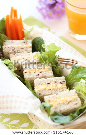 Boiled egg sandwich on multigrain bread with green leaf salad and carrot - stock photo