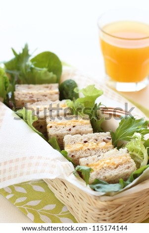Boiled egg sandwich on multigrain bread with green leaf salad and orange juice - stock photo