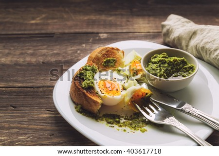Boiled egg with toasted bread and pesto sauce on rustic wooden background. Selective focus. - stock photo