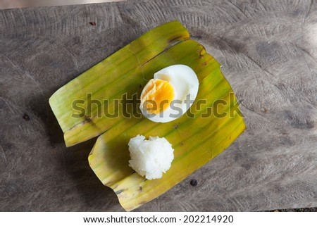 Boiled eggs, cooked rice on banana leaf. - stock photo