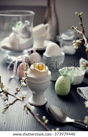 Boiled eggs for Easter breakfast. With easter decorations and blooming branch. Toned photo. - stock photo