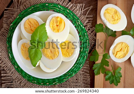 Boiled eggs in a bowl decorated with basil leaves - stock photo
