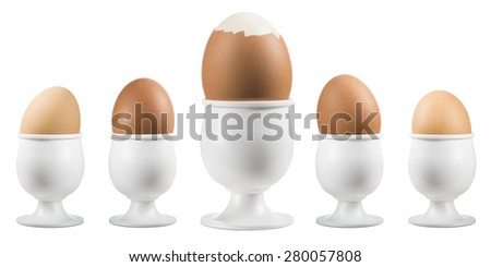 boiled eggs on eggcup in a row with broken one on white background - stock photo