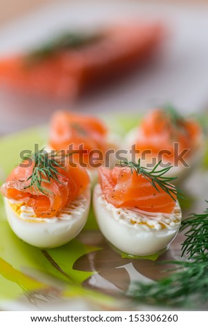 Boiled eggs with salted salmon and herbs - stock photo