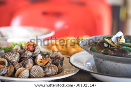 Boiled fresh cockles and mussels with fried egg for seafood background