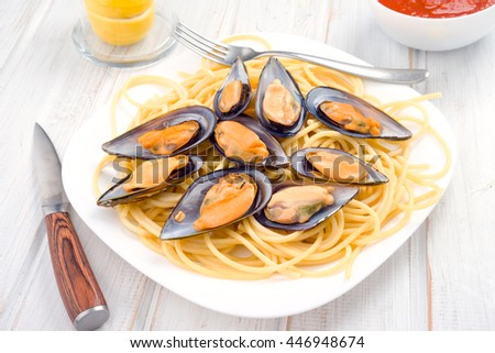 Boiled italian pasta with mussels on white wood - stock photo