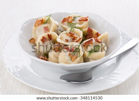 Boiled meat dumplings served with grilled bacon and dill. Traditional Russian pelmeni. - stock photo