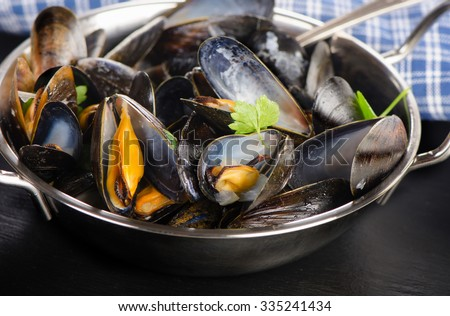 Boiled mussels in a cooking dish on a dark background. Selective focus