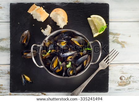 Boiled mussels in a dish on a dark background. Top view - stock photo