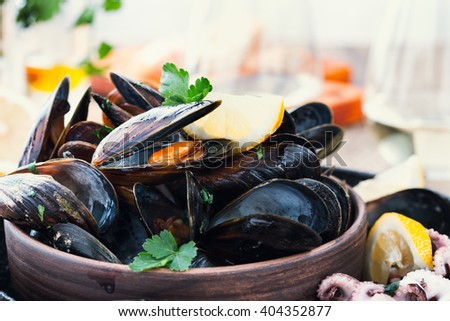 Boiled mussels in ceramic bowl and baby octopuses  garnished with fresh herbs on rustic wooden table ready to eat. Tasty seafood meal