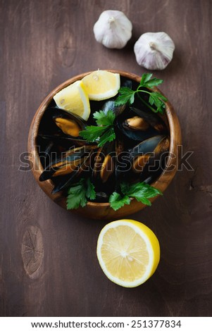 Boiled mussels served with lemon, parsley and garlic, above view - stock photo