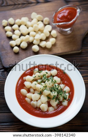 Boiled potato gnocchi served with tomato sauce, close-up - stock photo