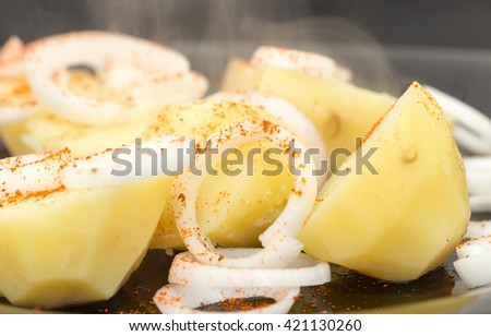 boiled potatoes and sliced onions on a plate