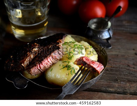 boiled potatoes, meat and tomatoes on a wooden background