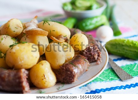 Boiled potatoes with slices of grilled sausage Closeup photo. - stock photo