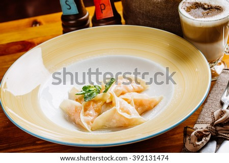 Boiled prepared homemade russian dumplings or pelmeni with pumpkin on the plate with fresh mint.cooking and food concept.