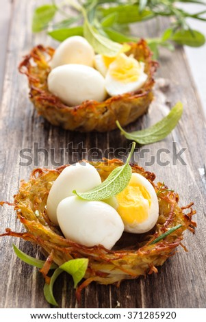 Boiled quail eggs in baked nests of potatoes. With sage and rosemary. - stock photo