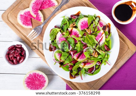 Boiled Red beans and watermelon radish salad with mix of lettuce leaves and walnuts on a white dish, with caramelized balsamic vinegar in a gravy boat, top view, close-up - stock photo