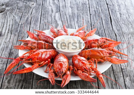 Boiled red crayfishes on a white dish with sauce of grated horseradish in a gravy boat and chilli pepper, on the old rustic table, close-up - stock photo