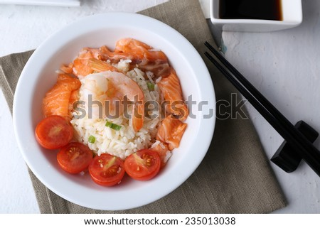 Boiled rice and shrimps, salmon and tomatoes in bowl, on wooden background - stock photo