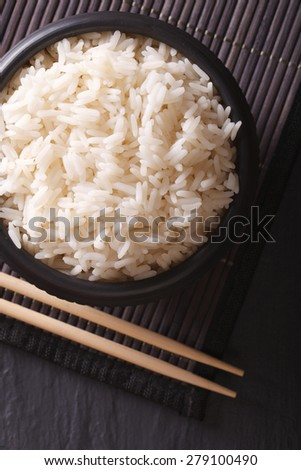 Boiled rice in a black bowl close-up and chopsticks. vertical top view  - stock photo