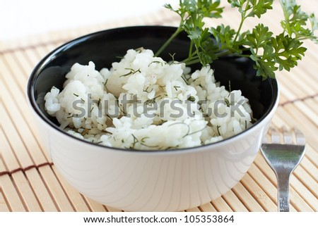 Boiled rice in black and white circular plate. Rice without the meat with dill and parsley