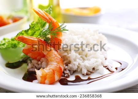 Boiled rice with shrimps served on table, close-up - stock photo