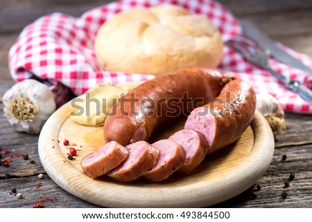 Boiled sausages on rustic round wooden board