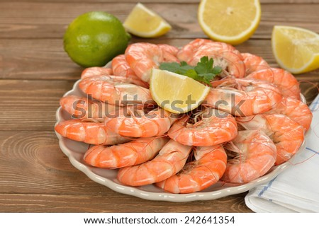 Boiled shrimp with lemon on a brown background - stock photo