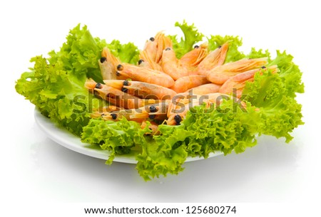 Boiled shrimps with lettuce leaves on plate, isolated on white