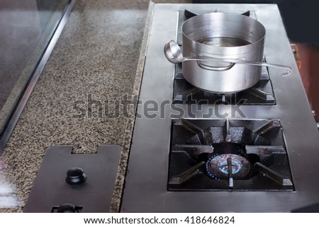 Boiled soup pot on gas stove in kitchen - stock photo