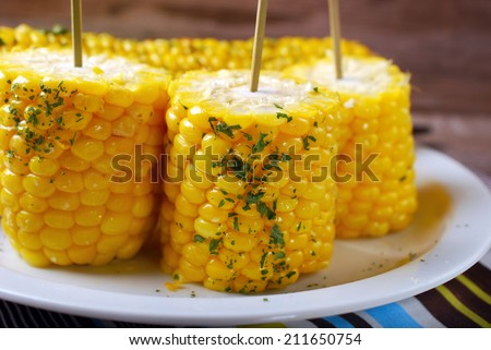 boiled sweet corn cobs with butter and herbs - stock photo