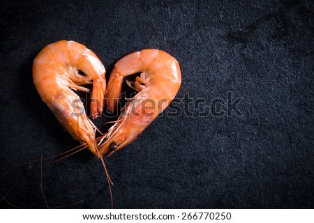 Boiled tiger shrimps heart shape on table with blank space on the right side   - stock photo