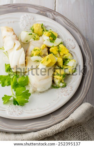 Boiled white fish cod with a sauce based on butter and boiled eggs with village greens and thyme. Served on a plate on a light wooden background.