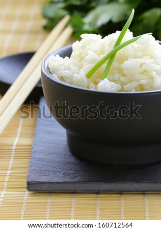 boiled white rice in a black bowl, Asian style - stock photo