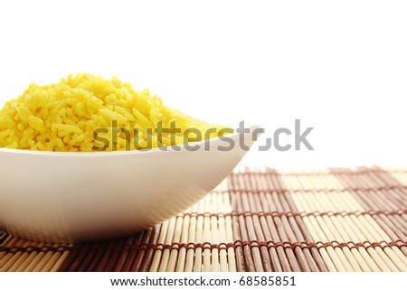 Boiled yellow rice boiled in white bowl. Plate stands on a wooden mat. Isolated on a white background - stock photo