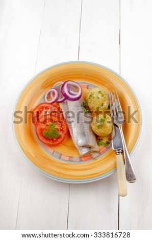 boiled young potato with parsley, tomato, lilac onion rings and sour herring on a plate - stock photo