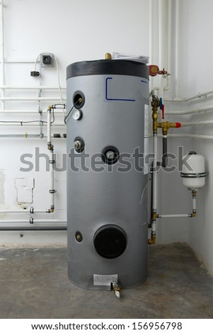 Boiler and pipes of the heating system of a house - stock photo